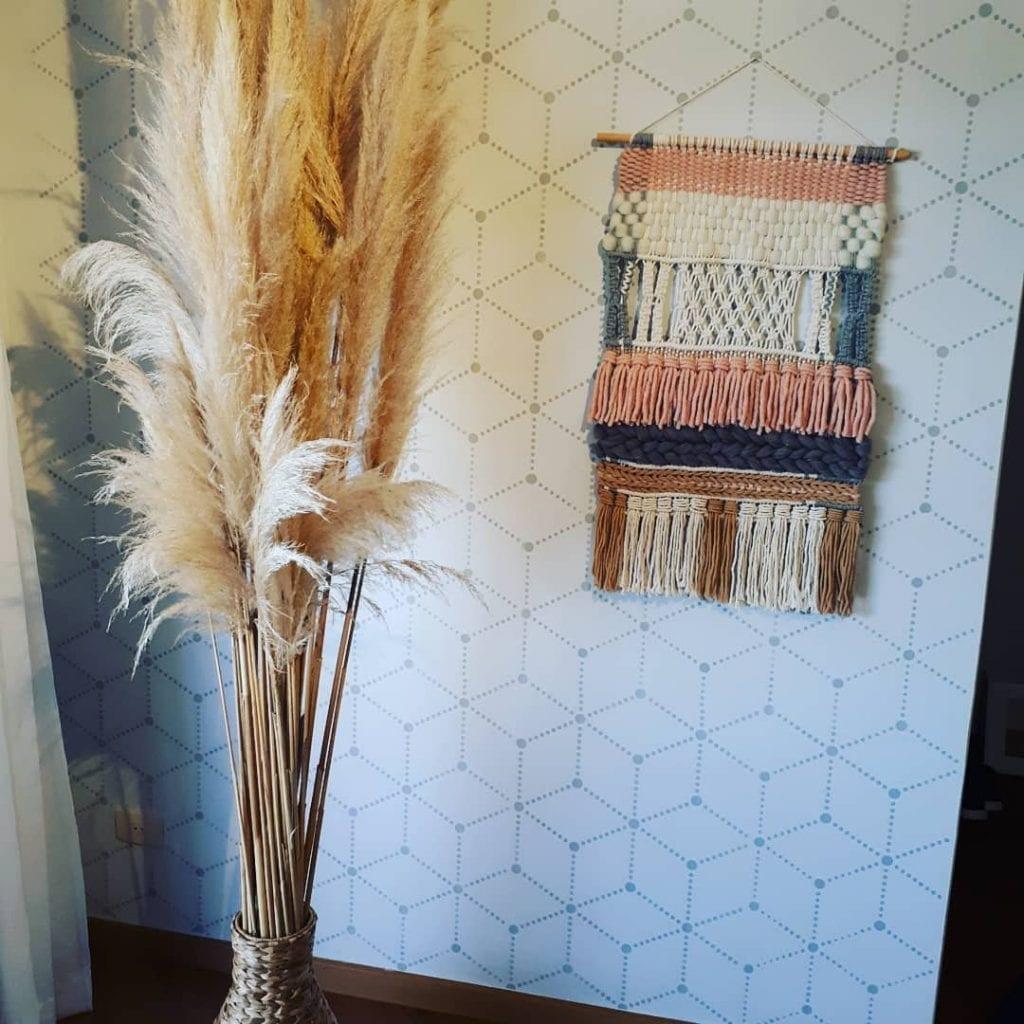 coin boho avec tapisserie et vase de branches sèches