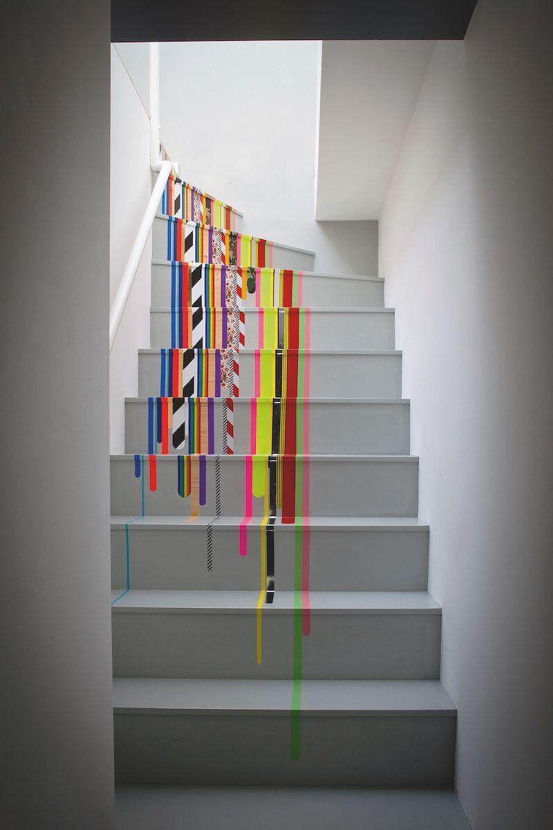 Décoration avec du ruban électrique: on dirait que de la peinture dégouline, mais c'est juste du ruban électrique coloré dans les escaliers