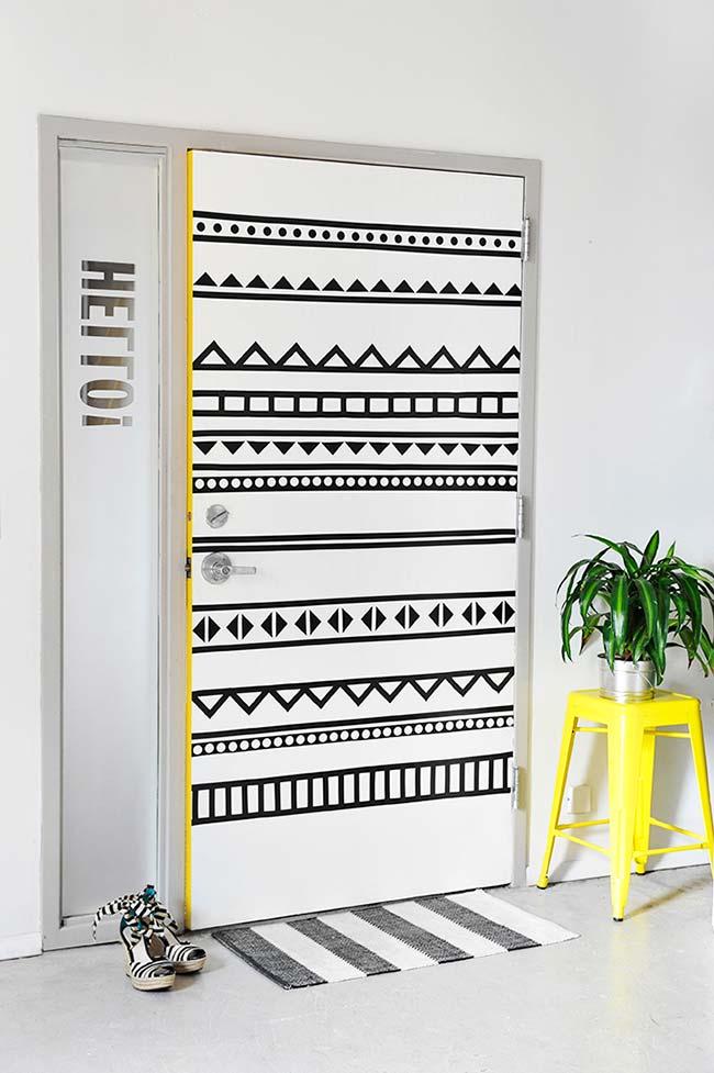 Porte décorée de ruban électrique;  le banc jaune à côté permet de mettre en valeur et d'améliorer le travail à la porte