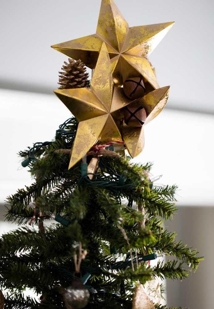 Étoile en papier avec des pommes de pin au sommet de l'arbre