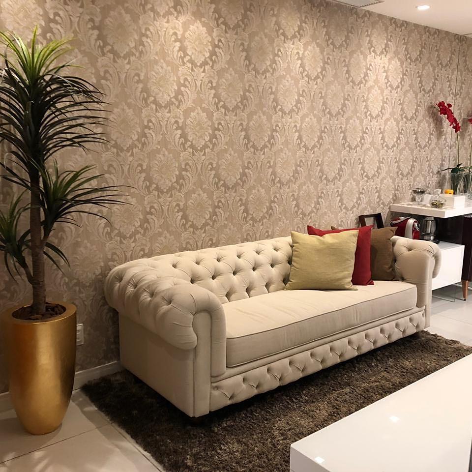 Canapé chesterfiel en velours beige clair dans le salon avec papier peint