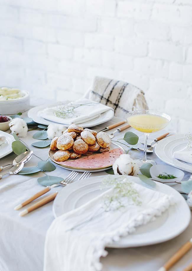 Une table simple, avec nappe et vaisselle blanches, gagne plus de charme avec des branches de feuilles naturelles
